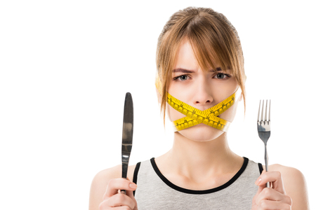 young woman with measuring tape tied around her mouth holding fork and knife isolated on white