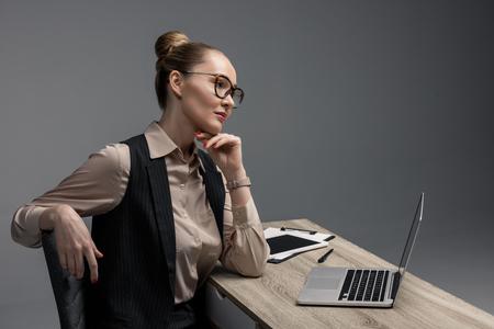pensive kazakh businesswoman in eyeglasses using laptop isolated on grey Stok Fotoğraf