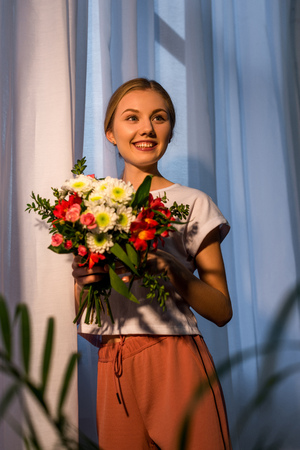 young woman with beautiful bouquet against window Stok Fotoğraf