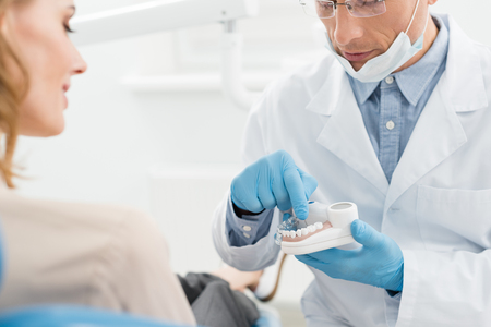 Doctor showing jaws model to female patient in modern dental clinic Banco de Imagens - 114248103