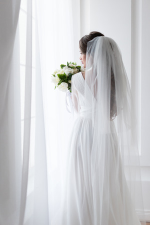 Rückansicht der brünetten Braut im Hochzeitskleid mit traditionellem Schleier und Blumenstrauß Standard-Bild