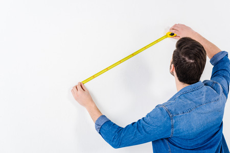 rear view of man measuring wall with tape measure on white 写真素材
