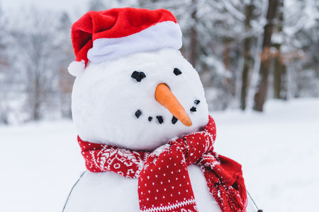 close-up view of funny snowman in scarf and santa hat in winter park Stock Photo