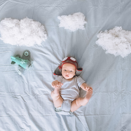 top view of adorable infant child in knitted pilot hat with toy plane surrounded with clouds made of cotton in bed Standard-Bild