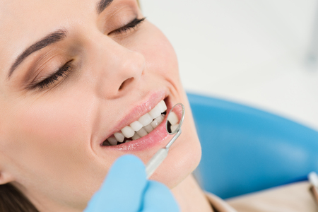 Doctor checking patient teeth with mirror in modern dental clinic Imagens