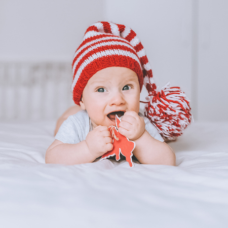 adorable infant child in red and white striped hat with pompom playing with toy angel in bed 写真素材