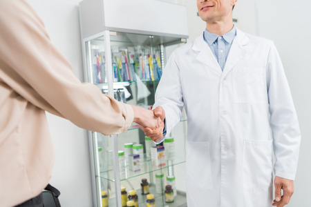 Close-up view of doctor and female patient shaking hands in modern dental clinic