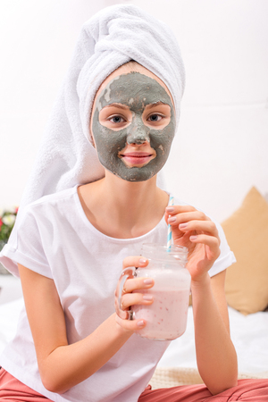 young woman with cosmetic clay mask drinking milkshake at home Foto de archivo - 114251308