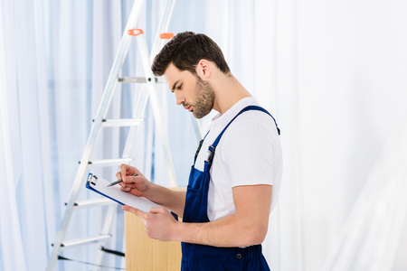 side view of thoughtful relocation service worker looking at clipboard