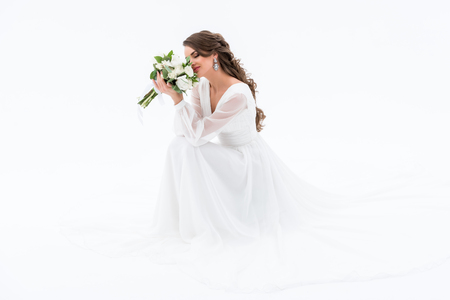 happy bride in traditional dress sniffing wedding bouquet, isolated on white Banco de Imagens