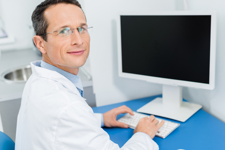 Smiling doctor in glasses working by computer in modern clinic Stock Photo