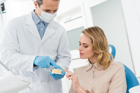 Doctor and patient looking at jaws model in modern dental clinic Imagens
