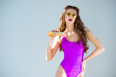 sexy attractive girl in ultra violet swimsuit holding hot dog isolated on grey