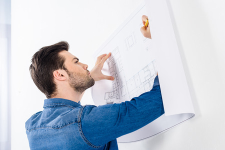 handsome architect writing on blueprint on white Stock Photo