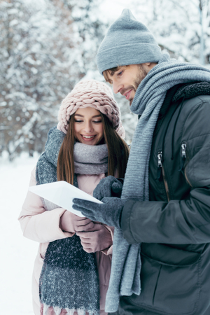 portrait of young happy couple with tablet in snowy park Stock Photo