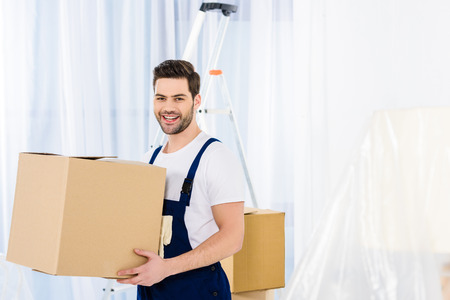 smiling relocation service worker holding box Banco de Imagens