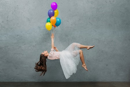 young woman levitating with colorful balloons Stock fotó