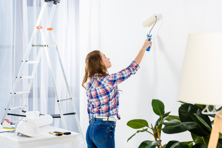 side view of girl painting wall with white paint