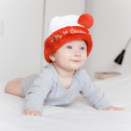 portrait of beautiful happy infant child in santa hat lying on bed and looking away