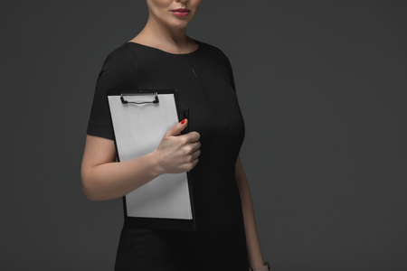 cropped shot of kazakh businesswoman holding clipboard isolated on grey
