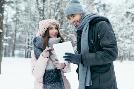portrait of young happy couple with tablet in snowy park Stock Photo - 114252095