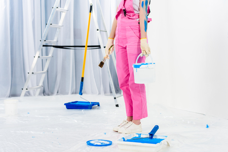 cropped image of girl holding paint brush and bucket with paint