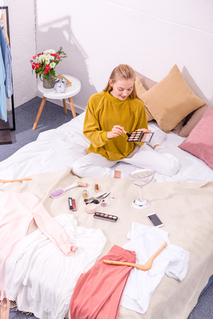 high angle view of young woman opening eye shadows box while sitting on bed Stock Photo - 114252173
