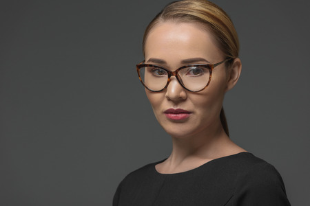 close-up portrait of beautiful kazakh woman in spectacles looking at camera isolated on grey