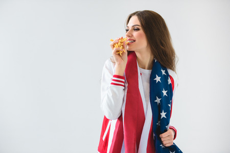 sexy smiling girl with usa flag eating french fries isolated on white Stock Photo