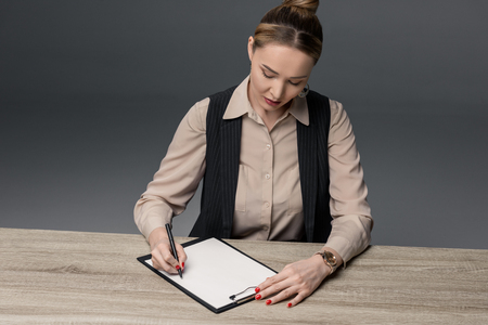attractive kazakh businesswoman writing on clipboard at table isolated on grey