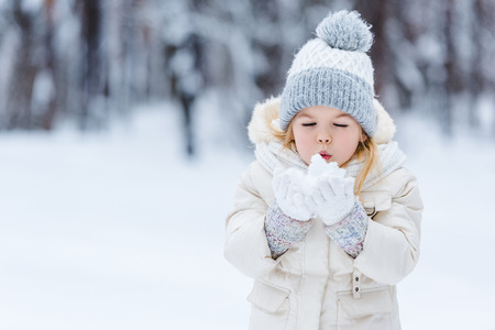 portrait of adorable kid blowing onto snow ball in hands in winter park Stock fotó