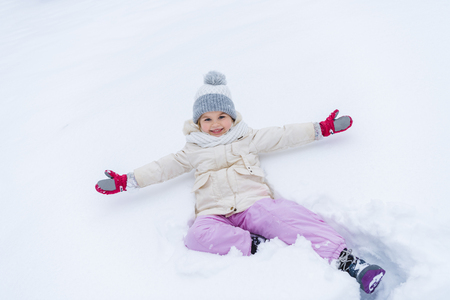 adorable little child with open arms lying on snow and smiling at camera