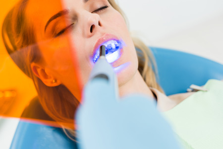 Female patient at dental procedure using uv lamp in modern dental clinic 写真素材