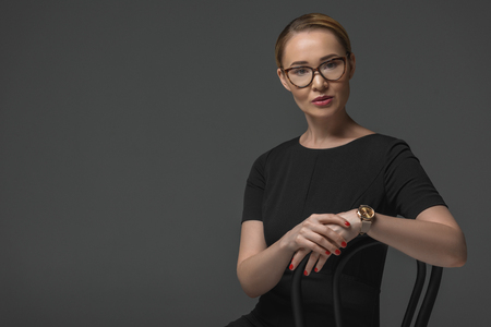 beautiful kazakh woman in eyeglasses sitting on chair and looking at camera isolated on grey