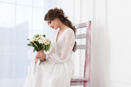 beautiful elegant bride sitting on big chair with wedding bouquet Stock Photo
