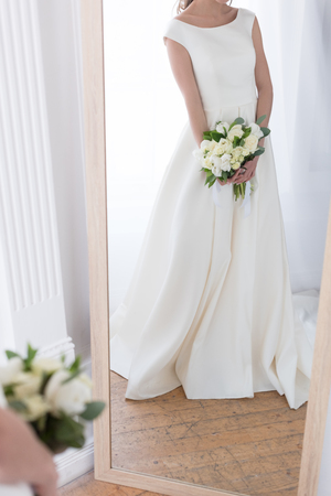cropped view of reflection of bride in traditional dress with wedding bouquet in mirror Stock Photo