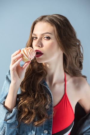 seductive woman in red swimsuit eating cupcake and looking at camera isolated on grey