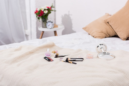 close-up shot of makeup supplies lying on bed 版權商用圖片