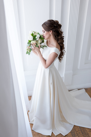 elegant bride in traditional white dress sniffing wedding bouquet Banco de Imagens