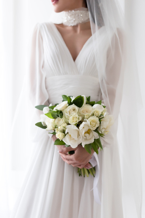 cropped view of bride in wedding dress and veil holding white bouquet Stock Photo