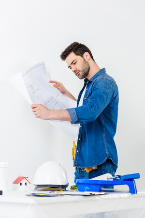 side view of man looking at blueprint