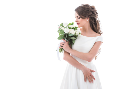 elegant bride posing in traditional white dress with wedding bouquet, isolated on white Stock Photo
