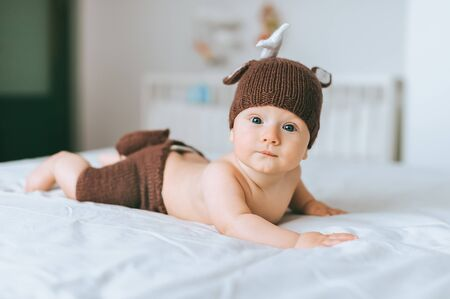 infant child in beautiful knitted deer costume looking at camera in bed