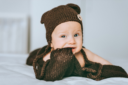 infant child in brown knitted hat biting blanket in bed