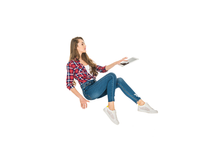 beautiful girl using digital tablet while levitating isolated on white