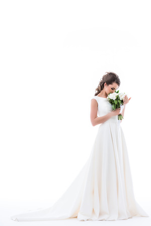 young bride in elegant white dress sniffing wedding bouquet, isolated on white Stock Photo