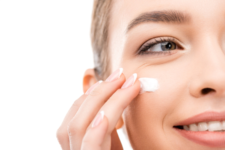 cropped view of young woman applying cosmetic cream, isolated on white