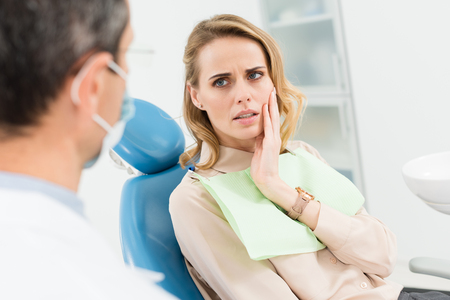 Female patient concerned about toothache in modern dental clinic 版權商用圖片