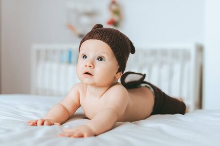 expressed infant child in knitted deer shorts and hat in bed Stock Photo