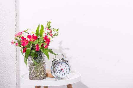 vintage alarm clock on table with flowers in vase 版權商用圖片